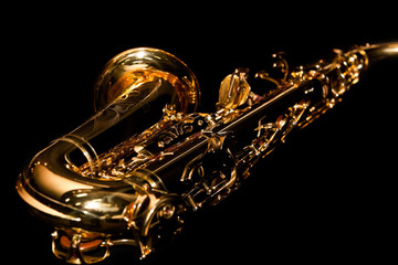 Lying saxophone on black background in dark colors