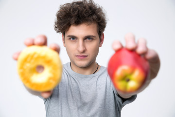 Casual young man holding apple and donut
