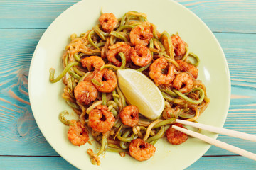 shrimps and zucchini noodles in green plate on blue wooden table
