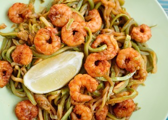 shrimps and zucchini cutting as noodles in green plate, close-up