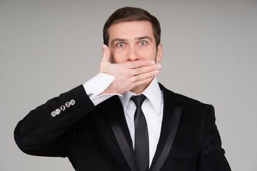 Business man making the speak no evil gesture. Businessman cover