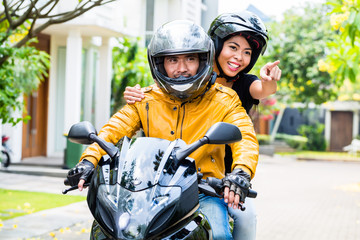 Couple with helmets riding motorcycle