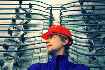 The worker in a helmet at factory.Industrial interior.