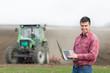 Farmer with laptop on field - 79693273