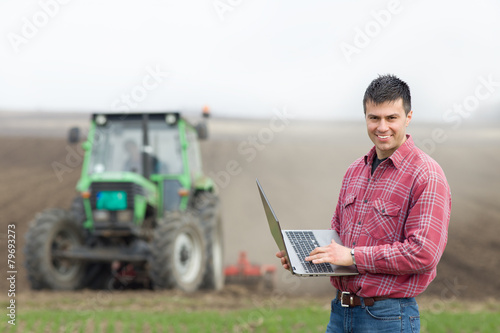 Farmer with laptop on field - 79693273