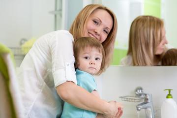 mother teaches kid washing hands in bathroom