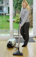 Frau reinigt Boden mit Staubsauger
