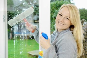 Frau putzt Fenster mit Fensterspray und Fensterwischer