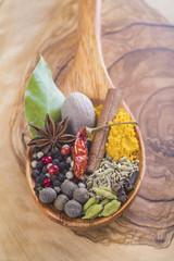 Hierbas y especias en cuchara de madera sobre tabla de coc