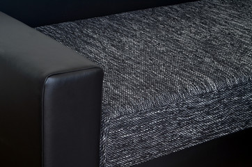 Detail of black leather armchair on black and white sofa