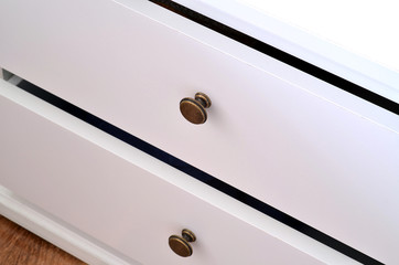 Detail of white laminated drawer with brass handle