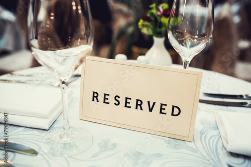 Reserved sign on a table in restaurant - 79696847