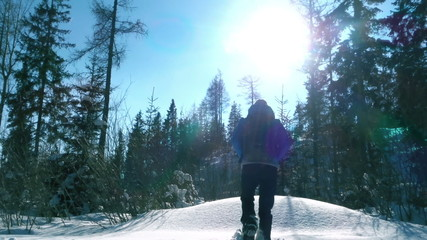 Young woman tourist standing on fresh snow and looking at view