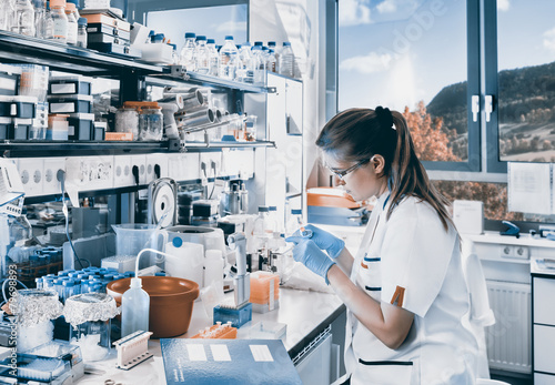 Young scientist works in modern laboratory - 79698893