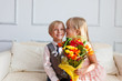 Girl with flowers is kissing boy.