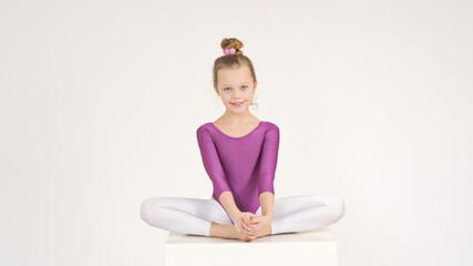 Flexible acrobatic girl sitting on light background