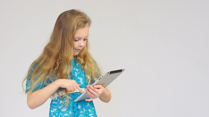 Beautiful girl in blue dress using digital tablet isolated