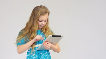 Beautiful girl in blue dress using digital tablet isolated on g