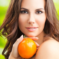 Portrait of woman with persimmon fruit, outdoor