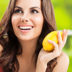 Happy young woman with lemon, outdoors