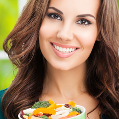 Portrait of smiling woman eating salad, outdoor