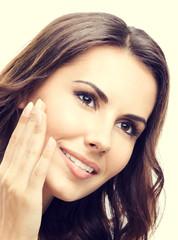 Smiling woman touching skin or applying cream