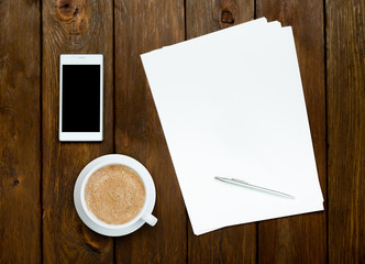 Smartphone, coffee and paper sheets