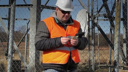 Engineer counting money at outdoors near metal structures