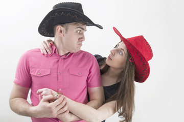 Young couple with cowboy hats making silly faces