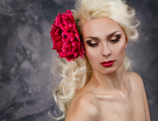 Beauty portrait of a blonde with a big red flower in her hair