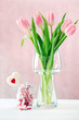 Beautiful pink tulips in vase with jar of paper
