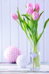 Beautiful pink tulips in vase with decorative balls