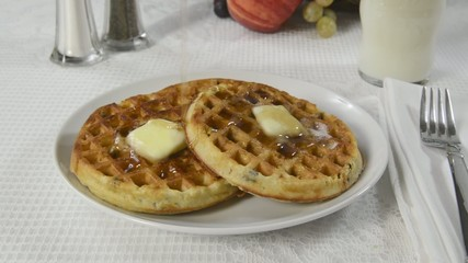 Pouring maple syrup on hot buttered waffles