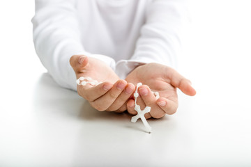 Child hands offer white rosary beads
