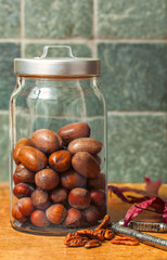 Glass jar of nuts in the shell with green marble backsplash