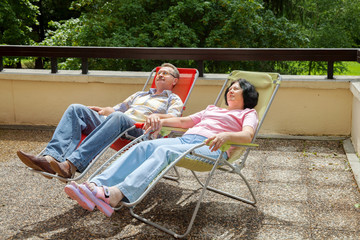 The elderly couple relax in lounges on sunny terrace