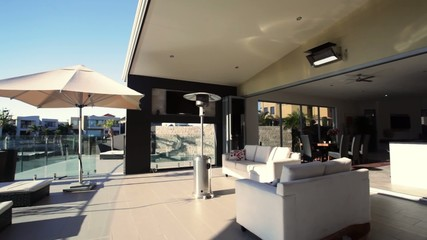 Dolly shot of luxury waterfront home with open entertaining area