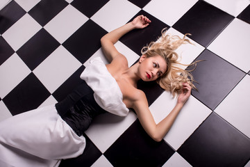 sexy blonde lying on the chessboard
