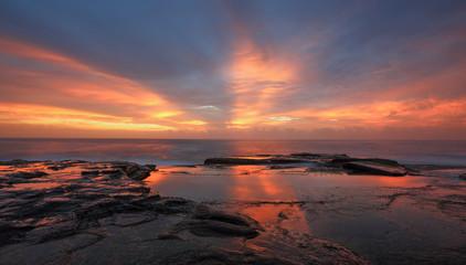 Streaks of orange red light at sunrise Curl Curl