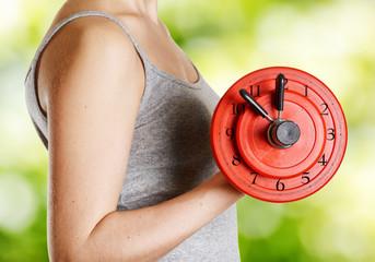 Beginner female athlete holding dumbbell with clock dial on natu