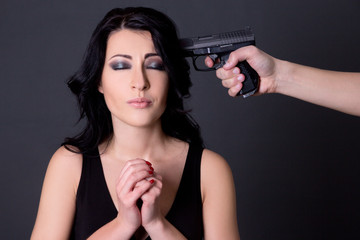 violence - young beautiful woman hostage and male hand with gun