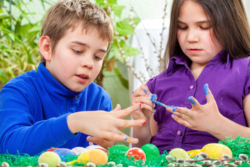 Mother and her children paint easter eggs