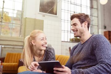 glückliches junges paar mit tablet zu hause
