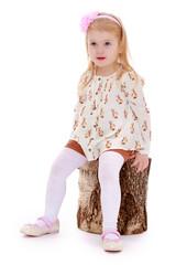 elegant beautiful girl sitting on a stump