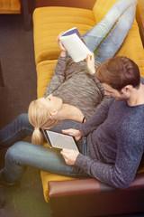 entspanntes paar liest zuhause auf dem sofa