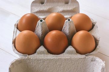 Fresh brown eggs in a carton