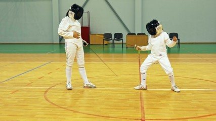 Little girl and trainer on a fencing training