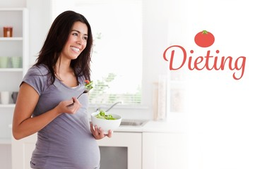 Beautiful pregnant woman holding a bowl of salad