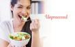 Unprocessed against happy businesswoman eating healthy salad
