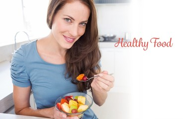Healthy food against smiling young woman eating fruit salad